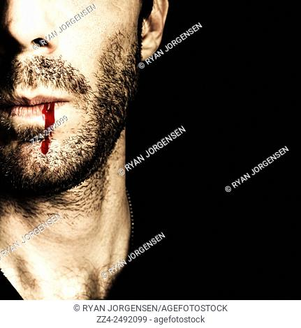 Dark half face portrait of a male vampire concealing remnants of an impassioned, all consuming affair of lust and betrayal. The kiss of death