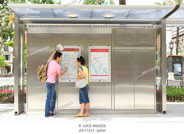 Couple looking at map at station, rear view
