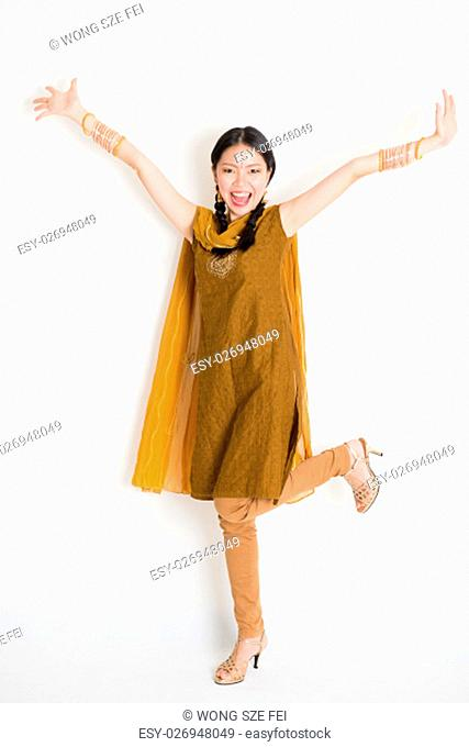 Portrait of excited mixed race Indian Chinese girl in traditional punjabi dress arms raised, full length standing on plain white background