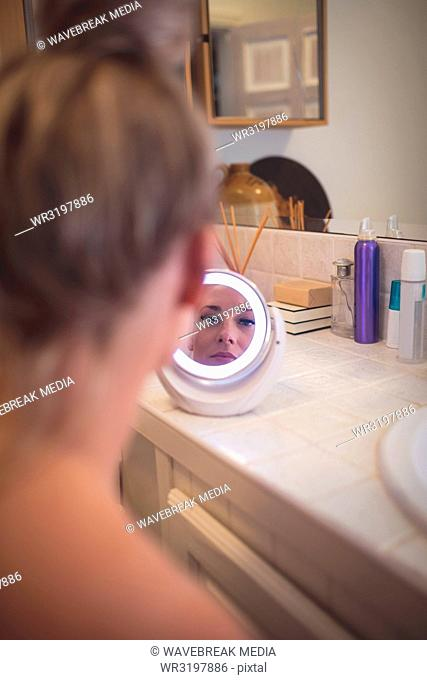 Woman looking in mirror at bathroom