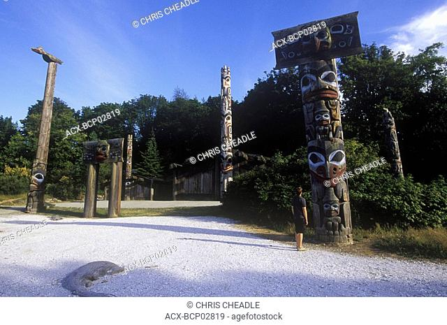 Boy looks at Totem poles on the grounds of the University of British Columbia Museum of Anthropology, British Columbia, Canada