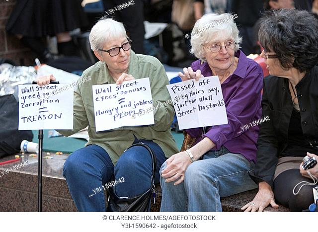 Women hold protest signs in Zuccotti Park during the Occupy Wall Street demonstration in New York City, New York, USA