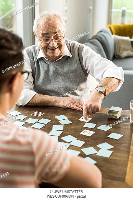 Senior man playing memory with his grandson