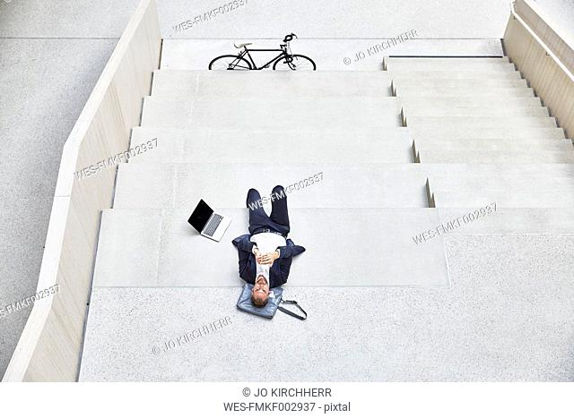 Businesssman lying on stairs next to laptop