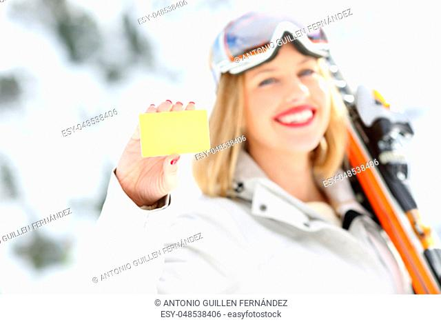 Front view portrait of a happy skier hand showing a card in a slope with a snowy mountain in the background
