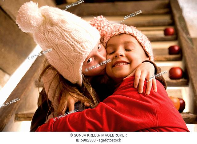 Two siblings sitting on the stairs of a cottage and are hugging