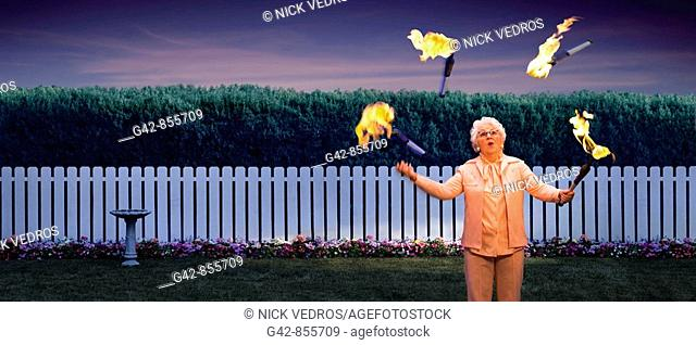 Grandmother juggling lit fire batons