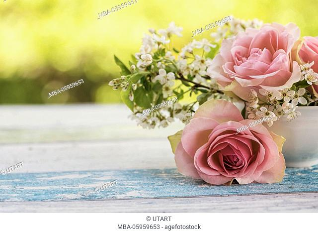 Flower arrangement of pink roses and small white blossoms in a small old white cup on wooden board with green background light