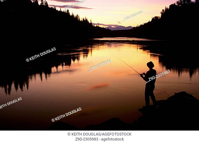 Angler fishing at sunset, Bulkley river, Smithers, BC, Canada