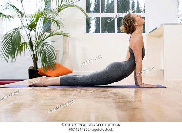 Healthy young woman doing the upward-facing dog yoga position
