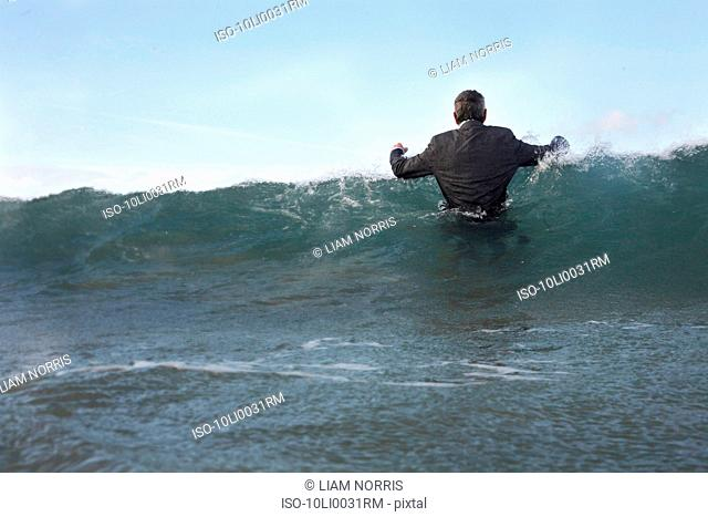 A businessman wading into the sea