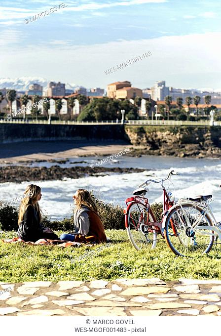 Two young women sitting near the sea with their bikes