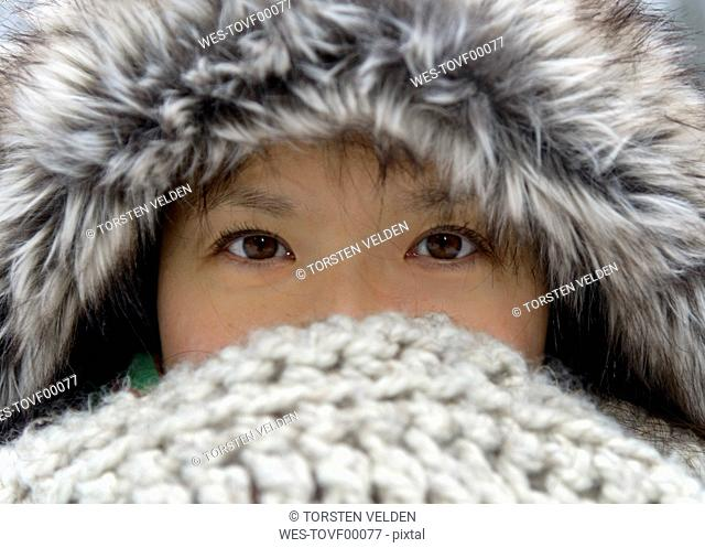 Portrait of woman wearing fur cap covering nose and mouth with scarf