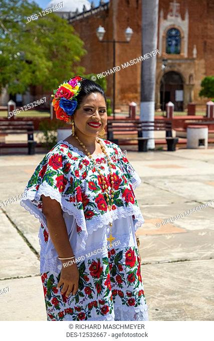 Mayan woman in traditional dress standing outside the Church of San Antonio de Padua, a former convent; Ticul, Yucatan, Mexico