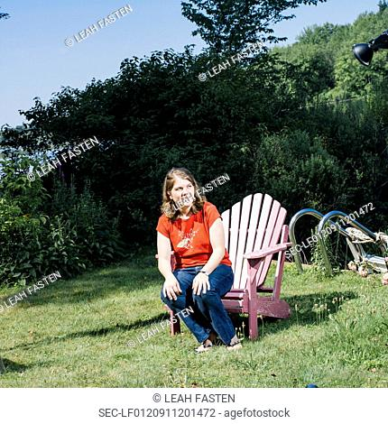 Woman sitting on edge of wooden chair on lawn