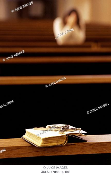 Rosary beads on an open Bible in church