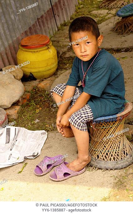little boy sitting outside his house , the nepalis , life in kathmandu , kathmandu street life , nepal