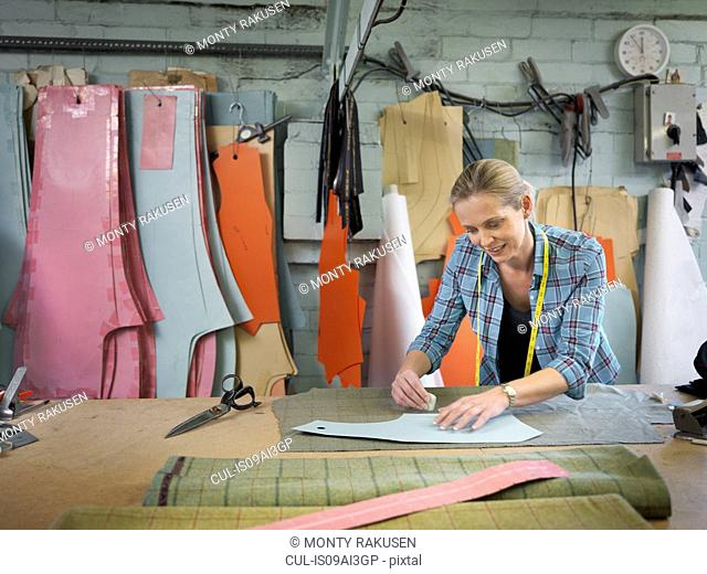 Fashion designer marking up cloth in clothing factory