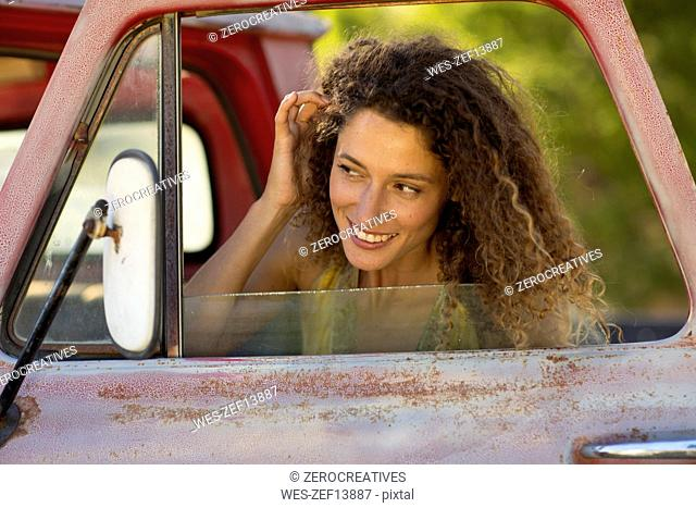 Happy young woman fixing her hair in car miror