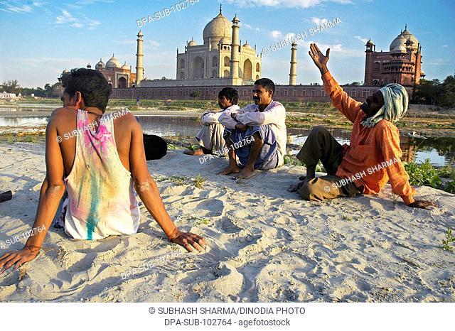 Local folk singer singing praises Taj banks river Yamuna flowing Taj Mahal Agra Ancient artist artistic beautiful blue sky clouds Color constructed 1631 A