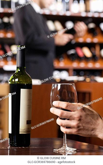 Man's hand holding a wine glass