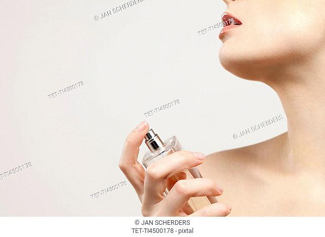 Close up of beautiful young woman spraying perfumes, studio shot