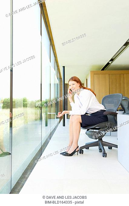 Caucasian businesswoman using cell phone in modern office