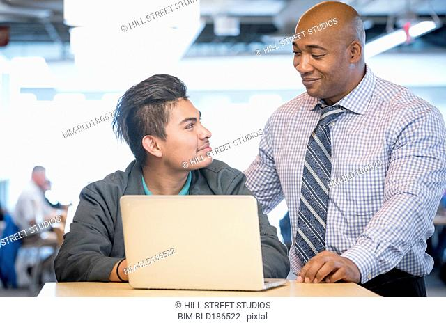 Mentor helping student use laptop