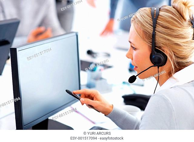 Female call center employee working on a computer with headset - copyspace