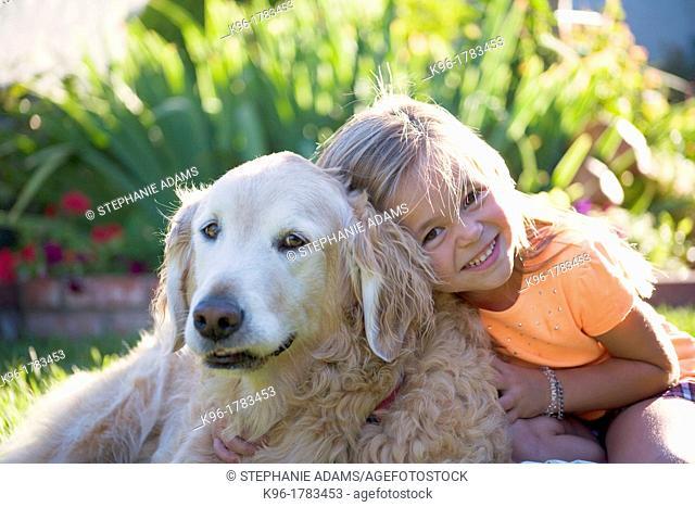 young girl hugging family dog