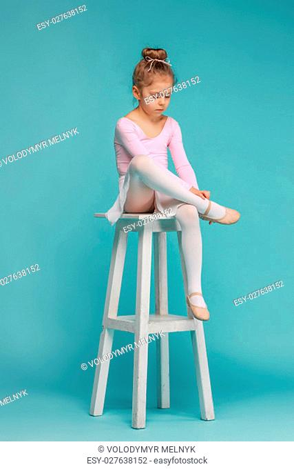 The little girl as balerina dancer sitting on white wooden chair at blue studio background