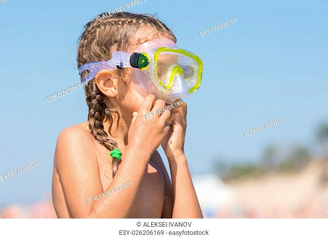 Six-year girl swims with a mask and snorkel under water at the seaside