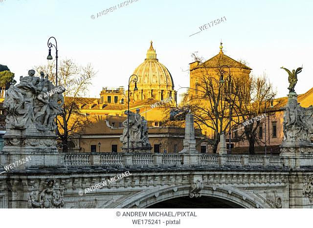 The sunrise hits St Peter's Cathedral and the Vatican but has yet to reach ponte vittorio emanuele II bridge in the foreground. Rome. Italy