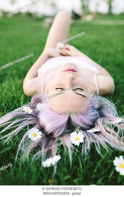 Woman lying on grass with flowers on hair