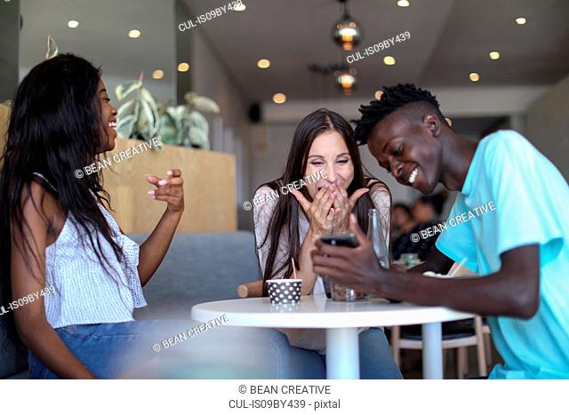 Friends using smartphone in ice cream parlour