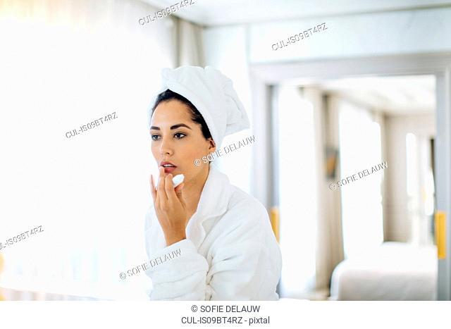 Woman applying lip balm in suite