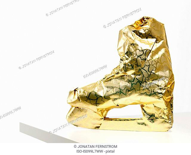 Gift wrapped ice skate against white background