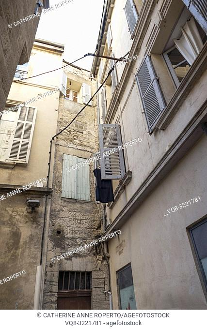 Looking upwards to a dark blue dress hung out to dry amongst the open louvred shutters and overhanging power cables in a narrow side street in old Avignon