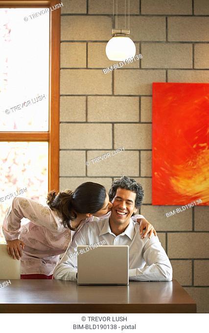 Woman kissing husband's cheek