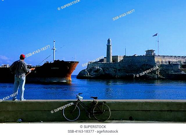CUBA, HAVANA, FISHERMAN, EL MORRO FORTRESS, LIGHTHOUSE, FREIGHTER ENTERING HARBOR