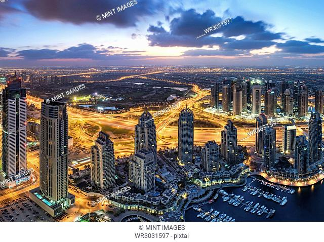 Aerial view of the cityscape of Dubai, United Arab Emirates at dusk, with skyscrapers and the marina in the foreground