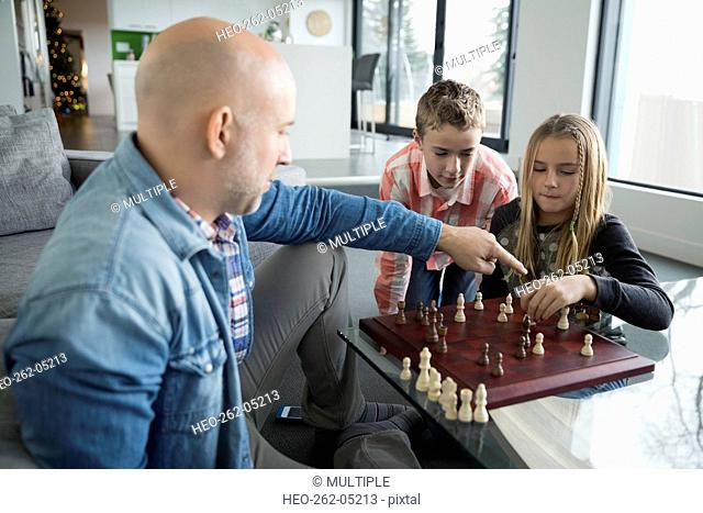 Father and children playing chess