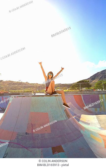 Asian woman cheering on ramp at skate park