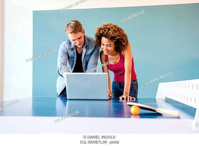 Couple looking at laptop on table tennis table