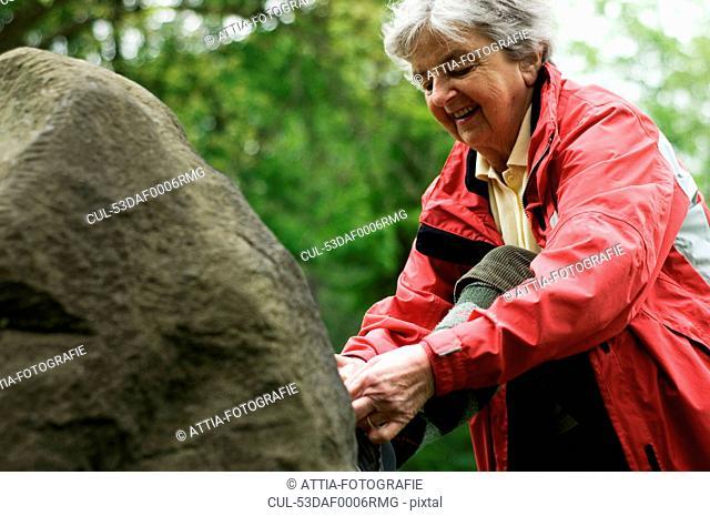 Older woman tying shoe on rock in park