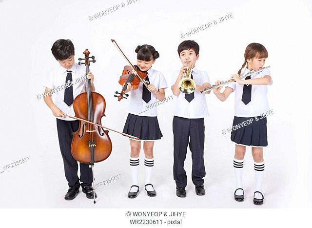 Four elementary school students in school uniforms standing and playing classical musical instrument each