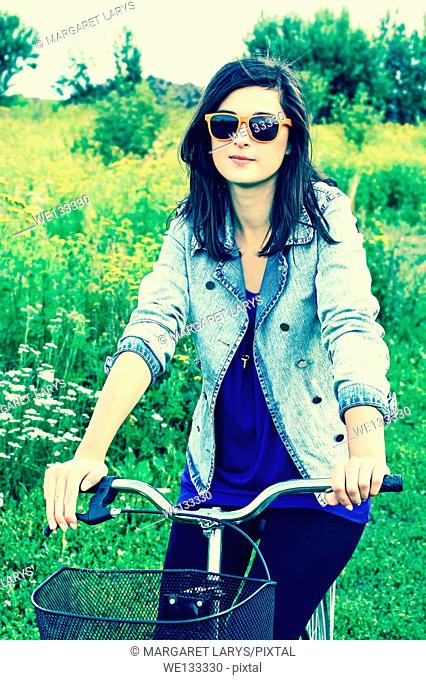 Beautiful young woman and a bike in the fields Beautiful young woman and a bike in the summer fields with wildflowers on a sunny summer day
