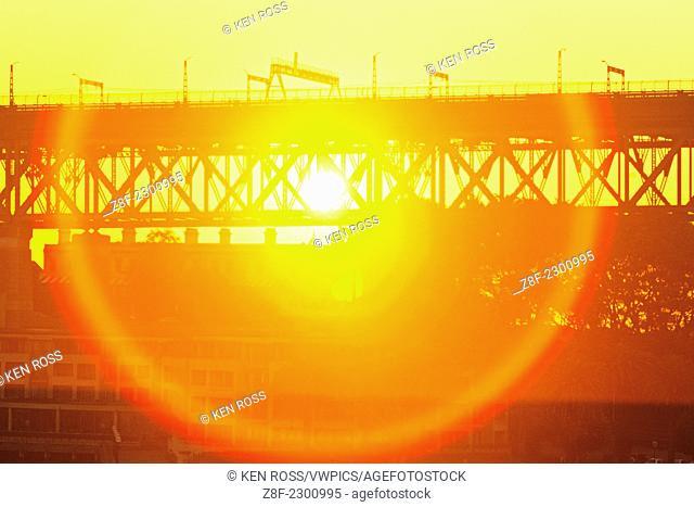 Sunburst through Sydney Harbour Bridge at sunset, Sydney, Australia