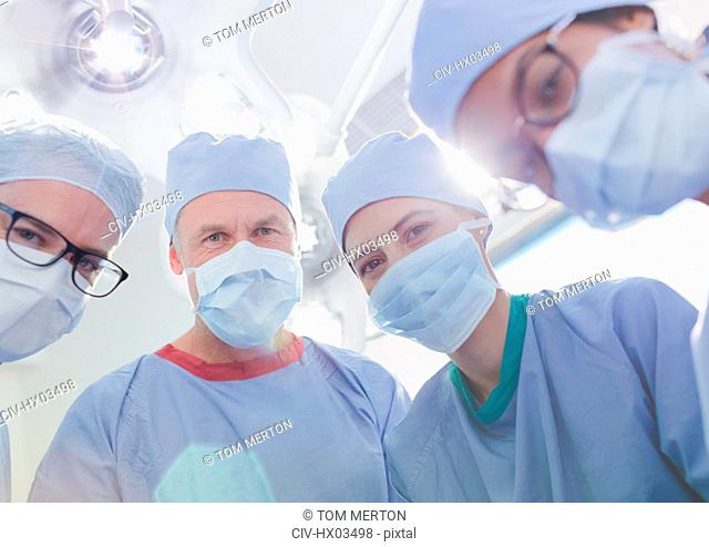 Portrait confident surgeons wearing surgical masks in operating room