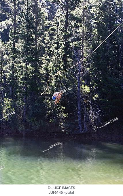Boy 8-10, in swimming shorts, letting go of rope swing above lake, hugging knees, side view